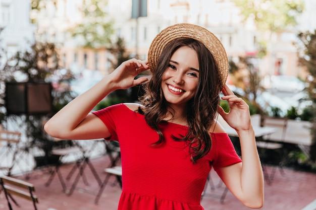 Brązowowłosa modelka pozowanie w słomkowym kapeluszu. zewnątrz zdjęcie wesołej dziewczyny w czerwonej sukience stojącej na mieście