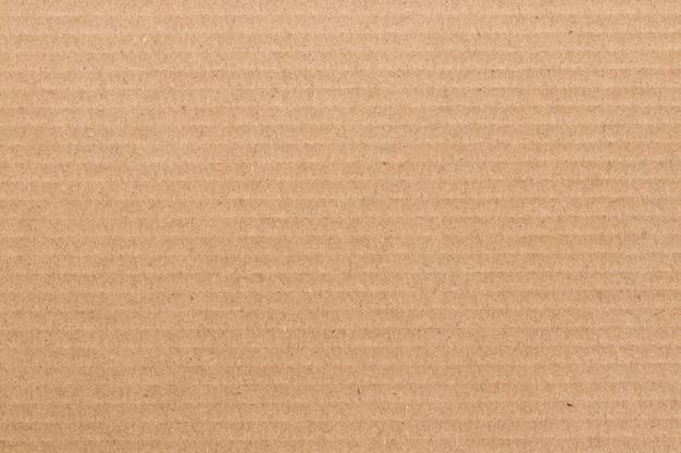 Brązowy arkusz tektury, tekstura kartonowego papieru z recyklingu.