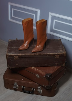 Brązowy but damski na trzech brązowych walizkach