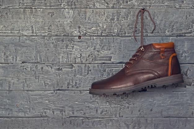 Brązowy but męski z lewą stopą wiszącą w drewnianej ścianie.