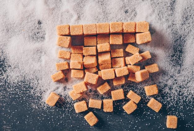 Brązowy cukier na cukrowym proszku i ciemnym stole. leżał płasko.