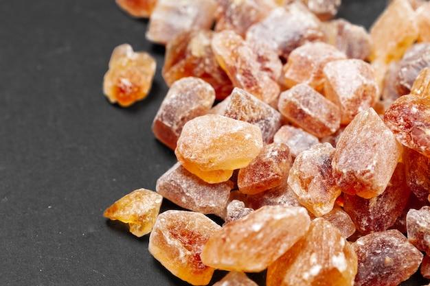 Brązowy cukier rock organiczny krystaliczny z bliska na ciemnym