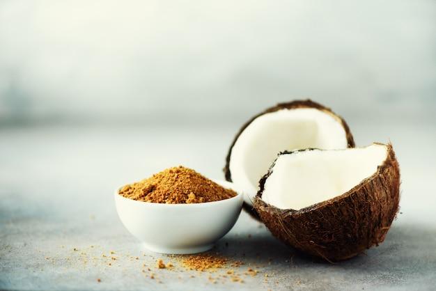 Brązowy cukier z palmy kokosowej i połowa owoców kokosowych na szarym betonie