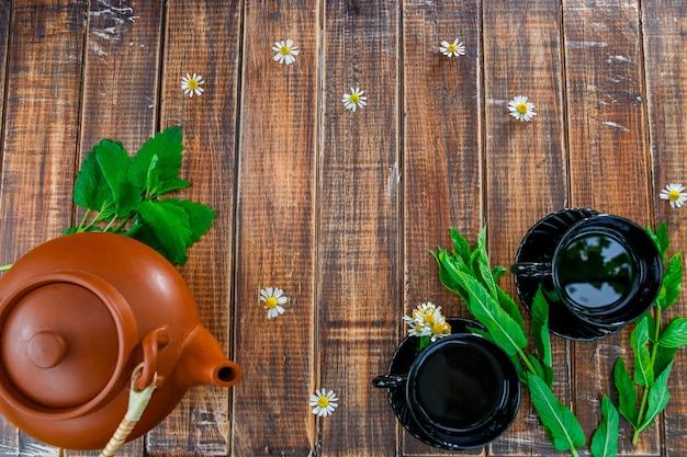 Brązowy czajniczek w pobliżu dwóch czarnych filiżanek herbaty na drewnianym stole ze świeżą miętą i rumiankiem. herbata . rama, lato. widok z góry.