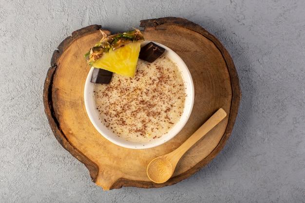 Brązowy deser czekoladowy z widokiem z góry z batonikami czekoladowymi plasterek ananasa na brązowym drewnianym biurku i szary