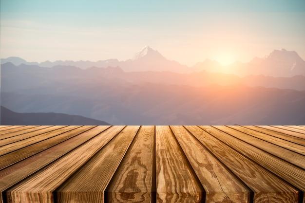 Brązowy drewniany blat na zamazanym szczycie w paśmie górskim o wschodzie słońca o poranku