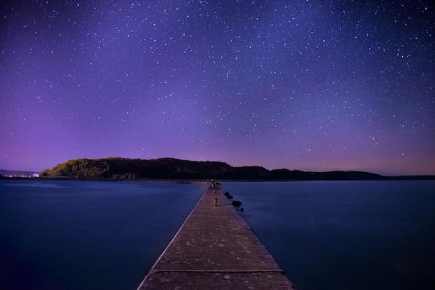 Brązowy drewniany dok pod nocnym niebem