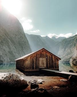 Brązowy drewniany dom w pobliżu jeziora i góry w ciągu dnia