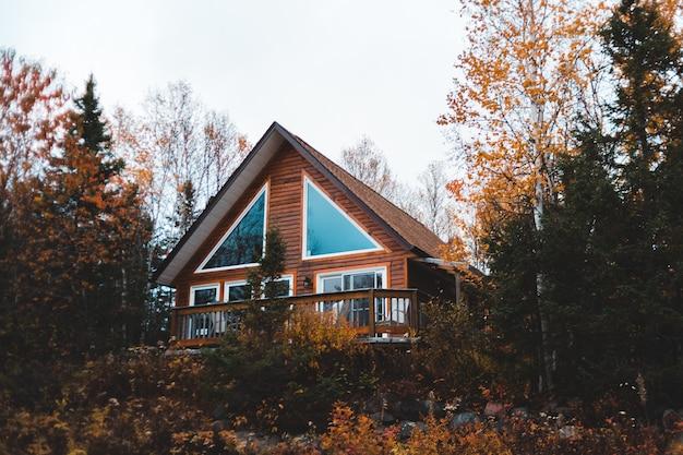 Brązowy drewniany dom w ramie ze szklanymi oknami
