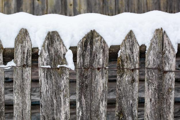 Brązowy drewniany płot wiejski pokryte śniegiem