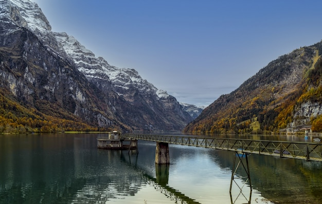 Brązowy drewniany pomost na jeziorze w pobliżu góry w ciągu dnia