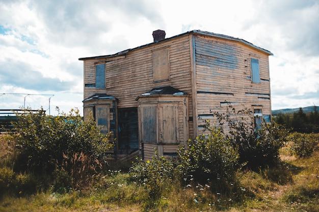 Brązowy dwupiętrowy dom w pobliżu roślin