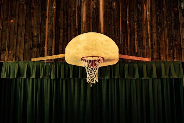 Brązowy i czerwony obręcz do koszykówki w pobliżu zielonych zasłon