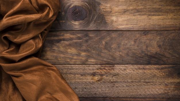 Brązowy jedwabny materiał na wyblakły drewniany stół