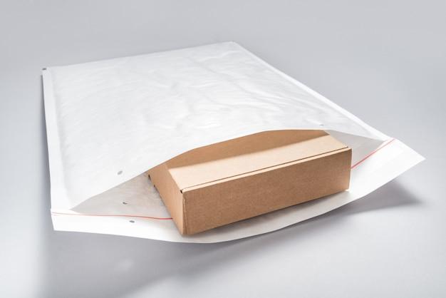 Brązowy karton zapakowany w białe koperty bąbelkowe na szarym tle