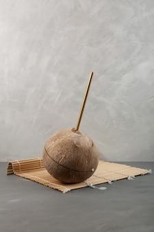 Brązowy kokos ze słomką do picia na szarym tle. woda kokosowa w prawdziwym orzechu.