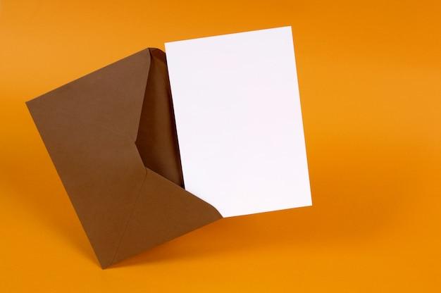 Brązowy koperty z pustą kartę listu lub zaproszenie samodzielnie na tle złota miejsce na kopię
