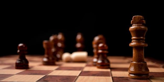 Brązowy król stojący naprzeciw szachownicy. nowi gracze biznesowi stoją przed wyzwaniami.