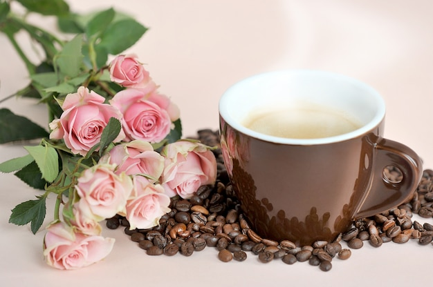 Brązowy kubek kawy, róże herbaciane i ziarna kawy