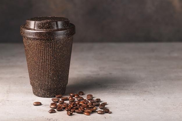 Brązowy kubek kawy wielokrotnego użytku z ziarnami kawy na szarym tle i brązowej ścianie