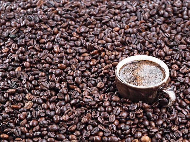Brązowy kubek z aromatycznym espresso stoi w ziarnach kawy. palone ziarna kawy. świeża aromatyczna ciemna kawa. zbliżenie.