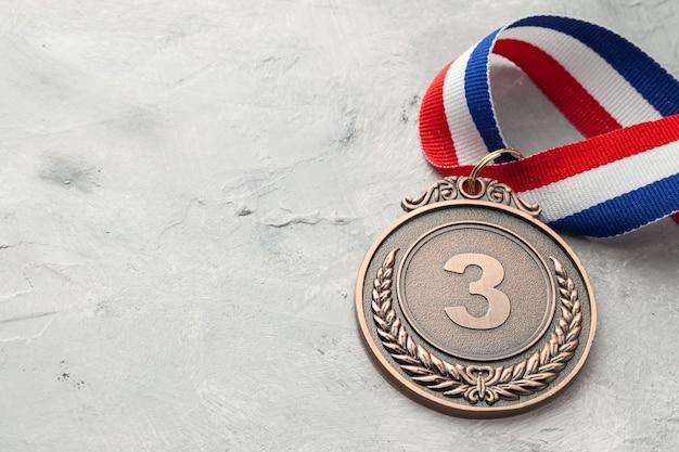 Brązowy medal. nagroda za iii miejsce ze wstążką.