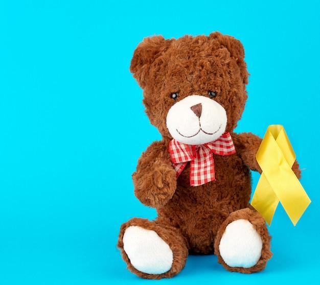 Brązowy miś siedzi i trzyma w łapie żółtą jedwabną wstążkę