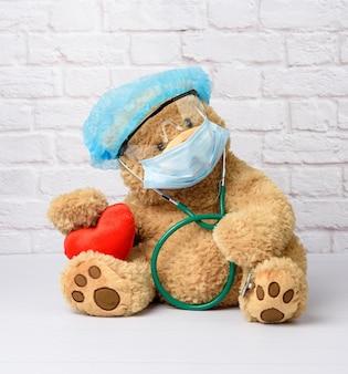Brązowy miś siedzi w ochronnych okularach z tworzywa sztucznego, jednorazowej masce medycznej i niebieskiej czapce na tle białego ceglanego muru. akcesoria ochronne przed wirusem podczas epidemii