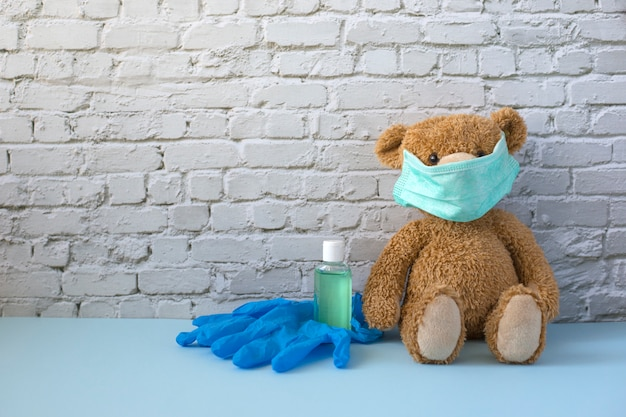Brązowy miś w masce medycznej siedzi obok butelki z alkoholowym żelem do rąk i niebieskimi gumowymi rękawiczkami. koncepcja koronawirusa