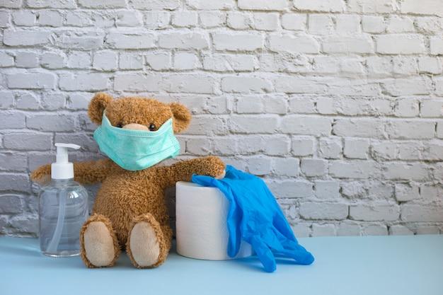 Brązowy miś w medycznej masce zawiera alkoholowy żel do rąk, rolkę papieru toaletowego i niebieskie gumowe rękawiczki.