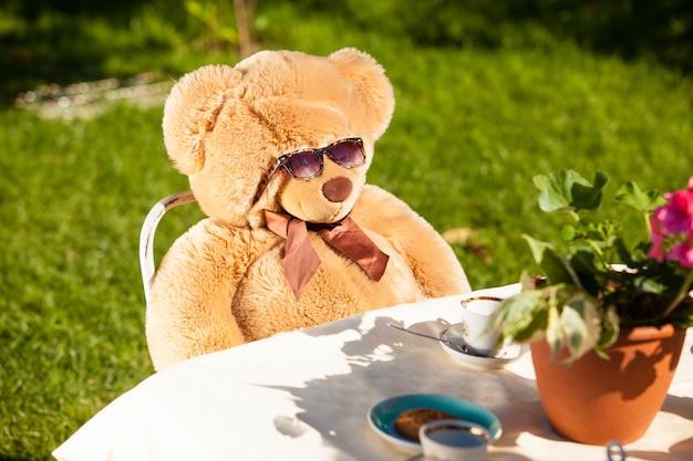 Brązowy miś w okularach przeciwsłonecznych jedzący śniadanie na świeżym powietrzu