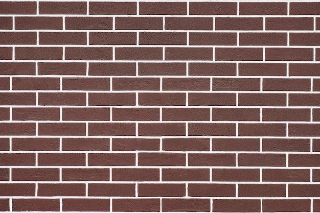 Brązowy mur z cegły z białymi liniami fugi.