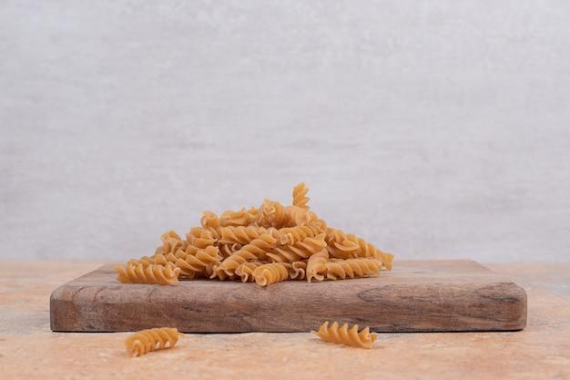 Brązowy, niegotowany spiralny makaron na desce. wysokiej jakości zdjęcie