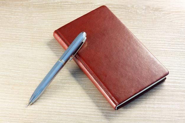 Brązowy notatnik z piórem na pulpicie