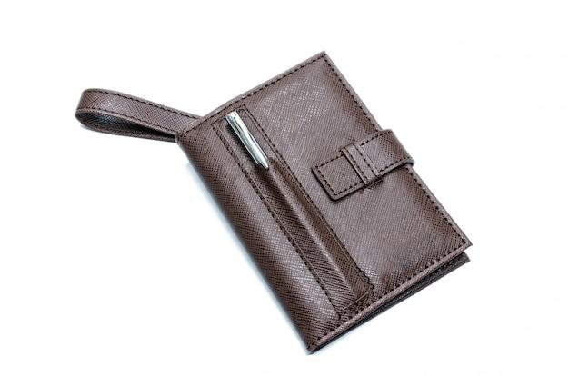 Brązowy notatnik ze srebrnym długopisem umieszczonym na notatniku.