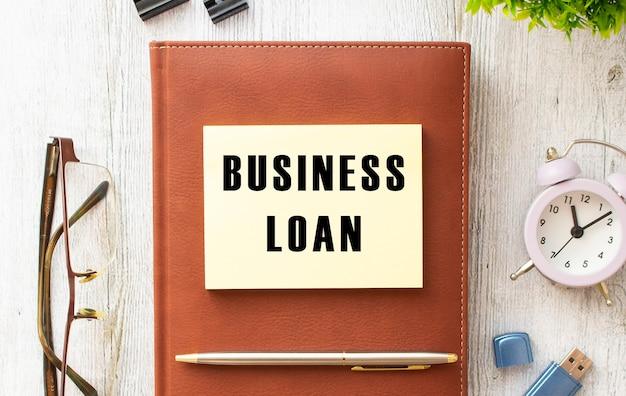 Brązowy notes, naklejka z napisem business loan, długopis, zegarek i okulary na drewnianym tle. pomysł na biznes.