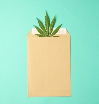 Brązowy papier koperta i zielony liść konopi na zielonym tle