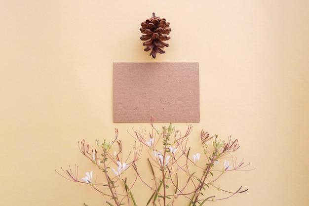 Brązowy papier na pastelowym żółtym tle ozdobione kwiatami i jodłami. wizytówka. wizytówka, biała księga. papierowe makiety. pastelowy kolor tła