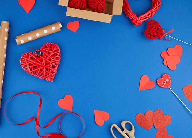 Brązowy papier pakowy, pakowane pudełko, czerwona wstążka, czerwone serce, zestaw przedmiotów do robienia prezentów.