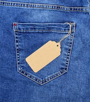 Brązowy papier pusta metka na liny na tylnej kieszeni niebieskich dżinsów