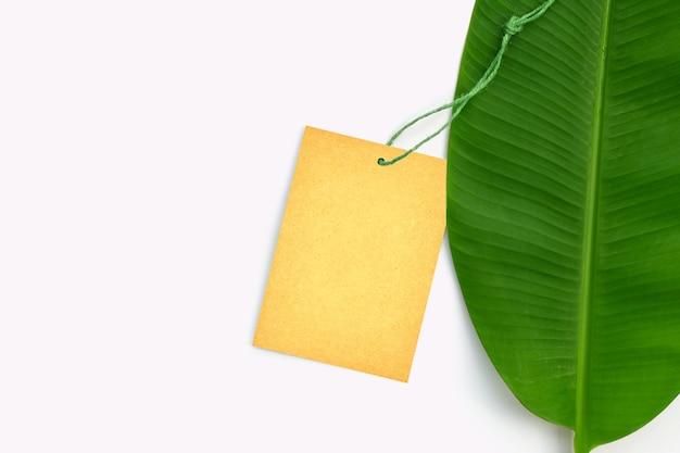 Brązowy papier z liściem bananowca na białym tle. skopiuj miejsce