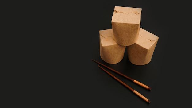 Brązowy papierowy kartonowy pojemnik na żywność na czarnym tle. dostawa azjatyckiego jedzenia. opakowanie na woka