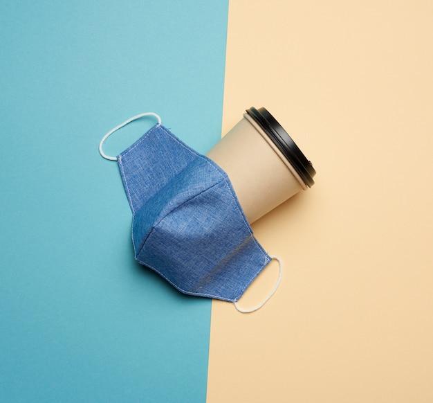 Brązowy papierowy kubek i niebieska maska wielokrotnego użytku na niebieskim tle