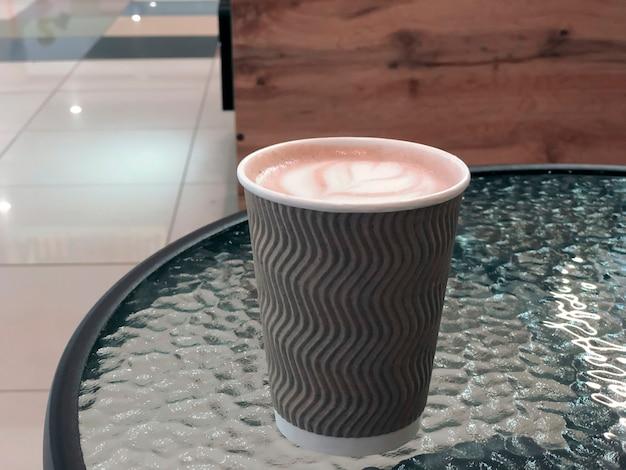 Brązowy papierowy kubek kawy z pianką w formie serca na szklanym stole w kawiarni. zbliżenie napojów kawowych.