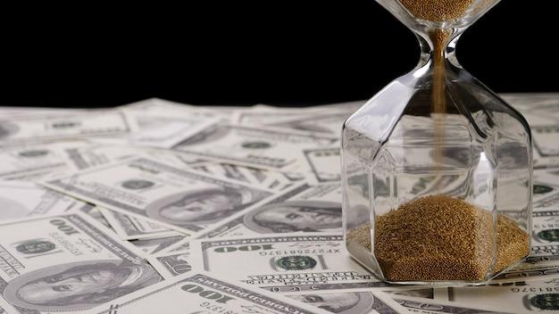 Brązowy piasek leje w jasne klepsydra na banknoty