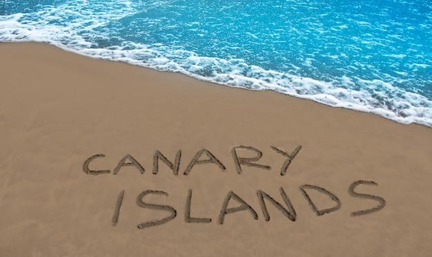 Brązowy piasek na plaży napisane słowo wyspy kanaryjskie