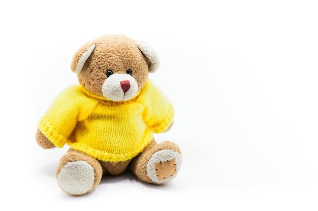 Brązowy pluszowy miś nosi żółte koszule siedząc na białym tle