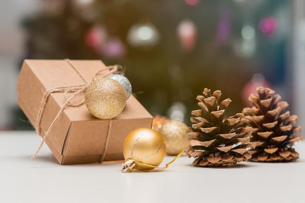 Brązowy prezent świąteczny, kule dekoracji i szyszki na stole.
