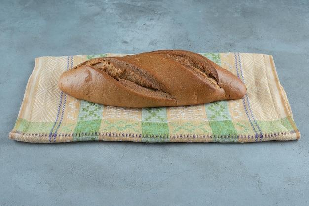 Brązowy pyszny chleb na kolorowym obrusie.