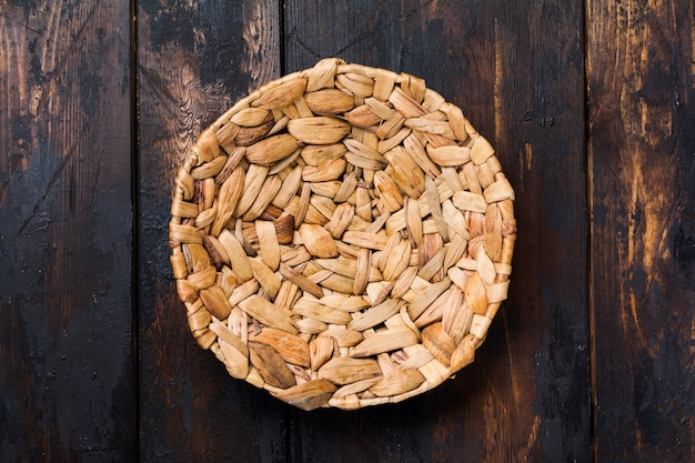 Brązowy rattanowy talerz i drewniana łyżka na stare drewniane tła. ustawienie stołu.